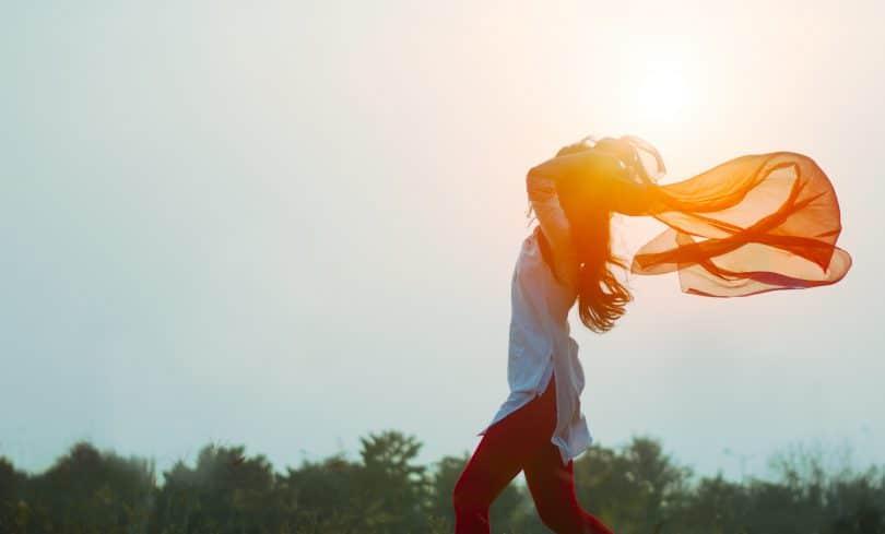 Mulher sentindo o vento bater com roupa voando e sol ao fundo