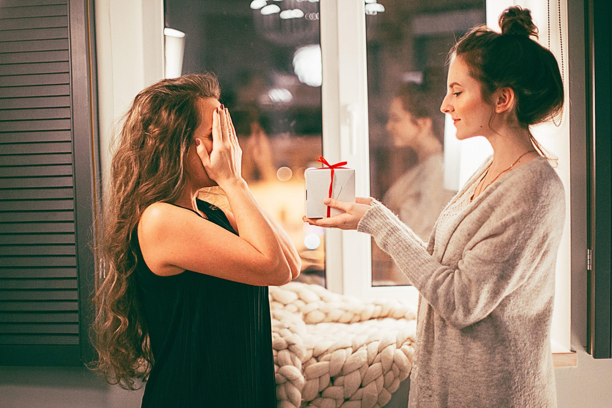 Mulher com mãos nos olhos recebendo presente de outra mulher