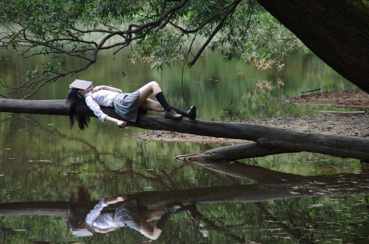 Mulher deiatda em galho de árvore