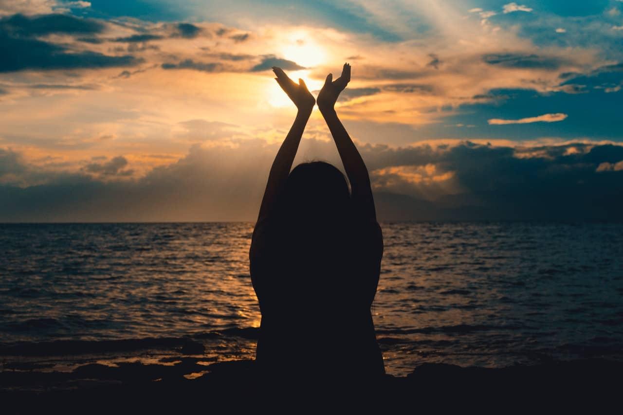 Silhueta de mulher com mãos para o alto e pôr-do-sol ao fundo