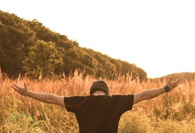 Homem de costas com braços abertos e campo ao fundo