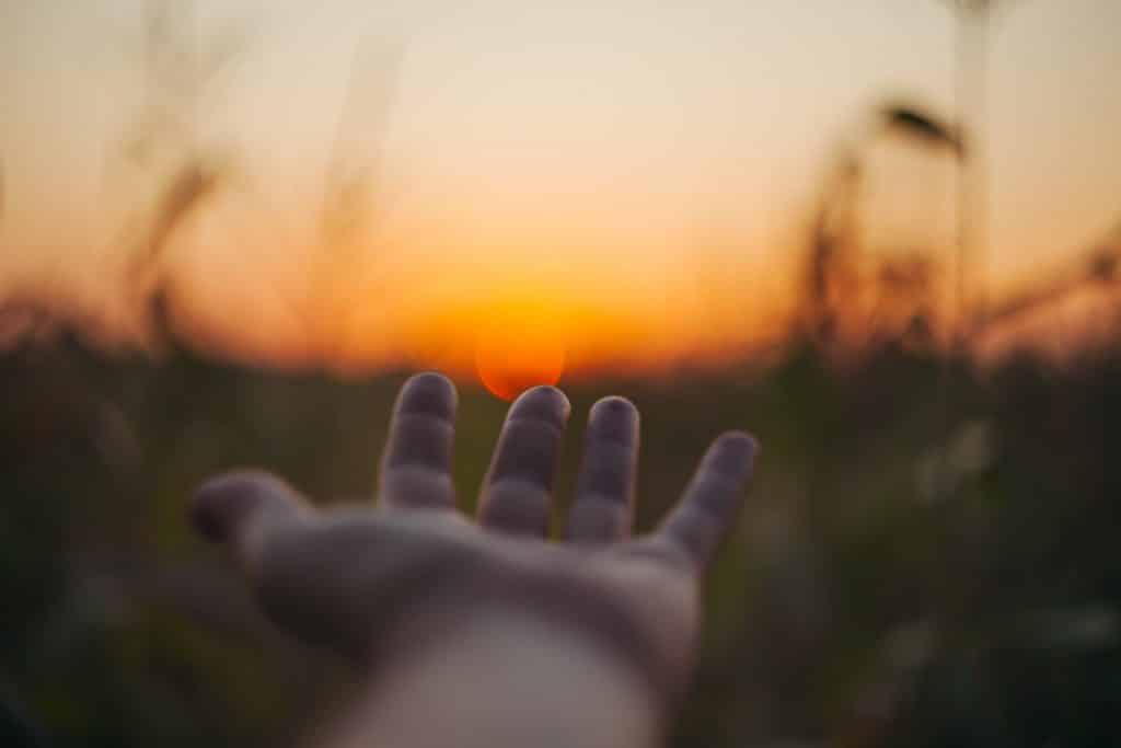 Pessoa com a mão em direção ao sol em um campo aberto de gramado