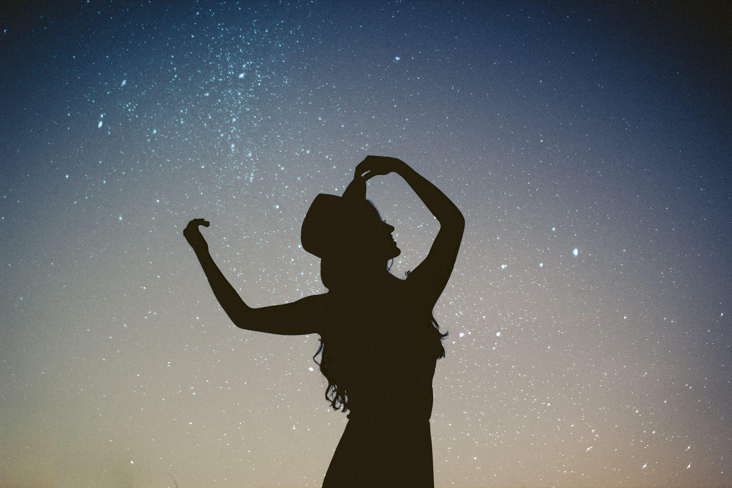 Silhueta de mulher com céu estrelado ao fundo