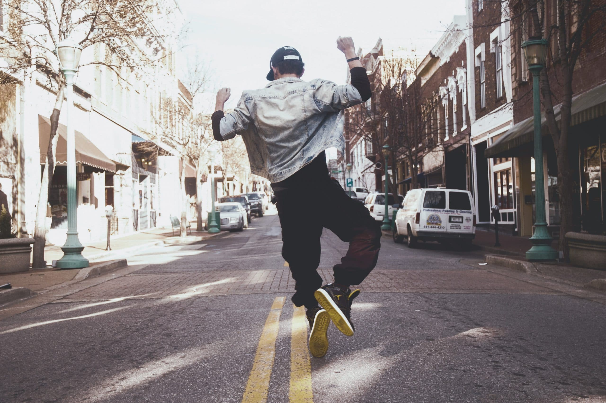 Homem de costas pulando no meio da rua