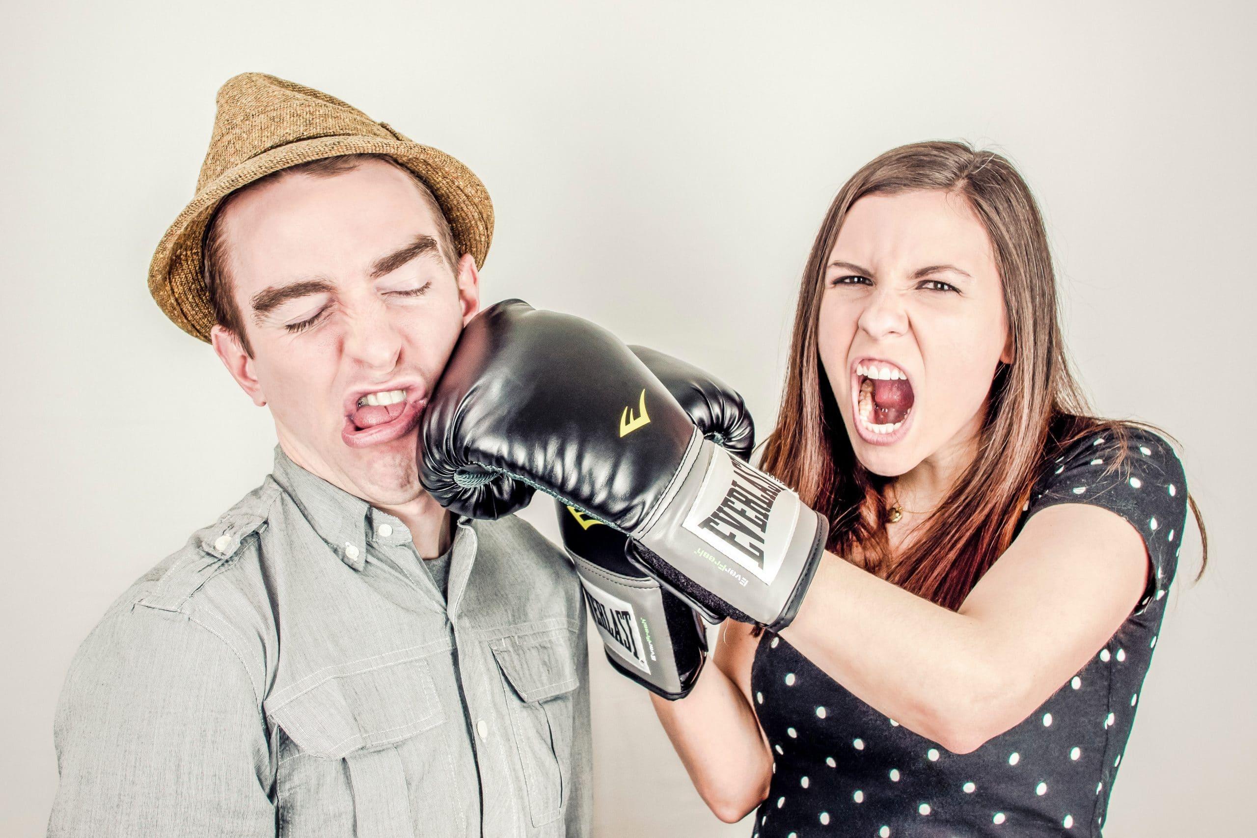 Mulher com luvas de boxe batendo em rosto de homem