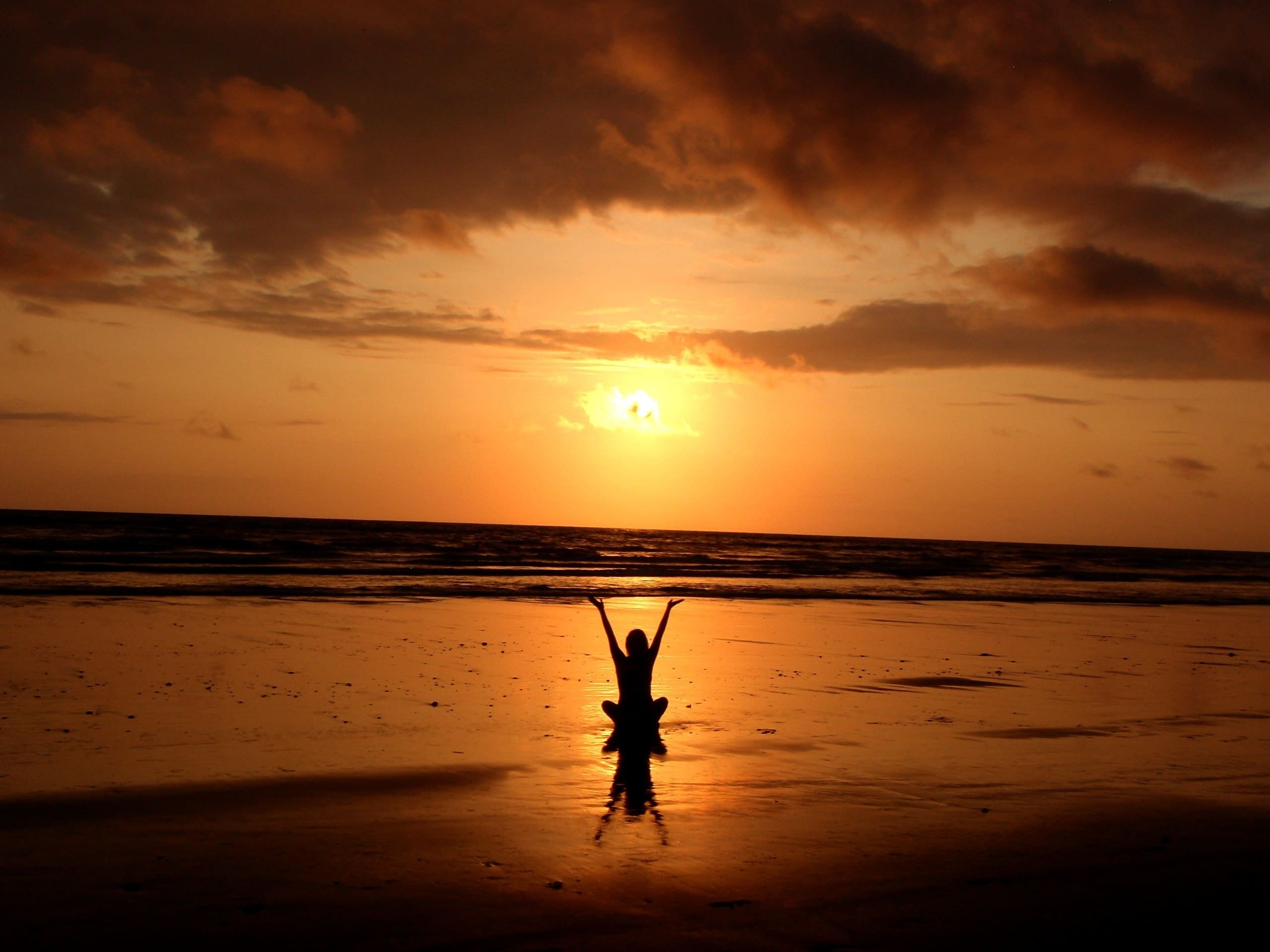 Silhueta de pessoa sentada na praia com braços para o alto
