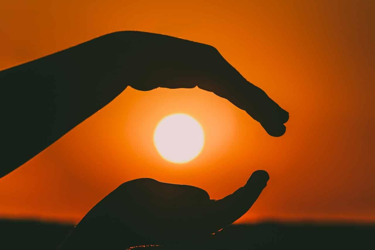 Silhueta de mãos com sol ao fundo