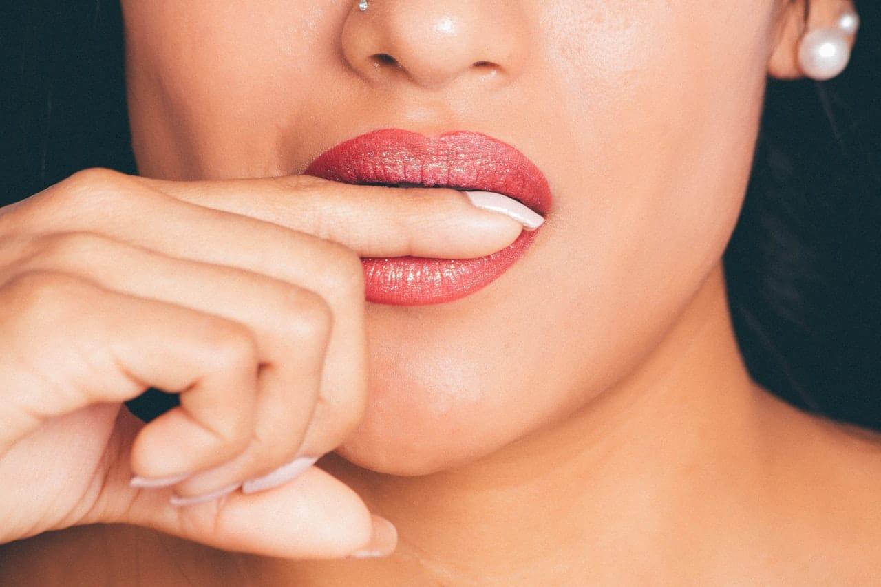 Meio rosto de mulher com dedo na boca