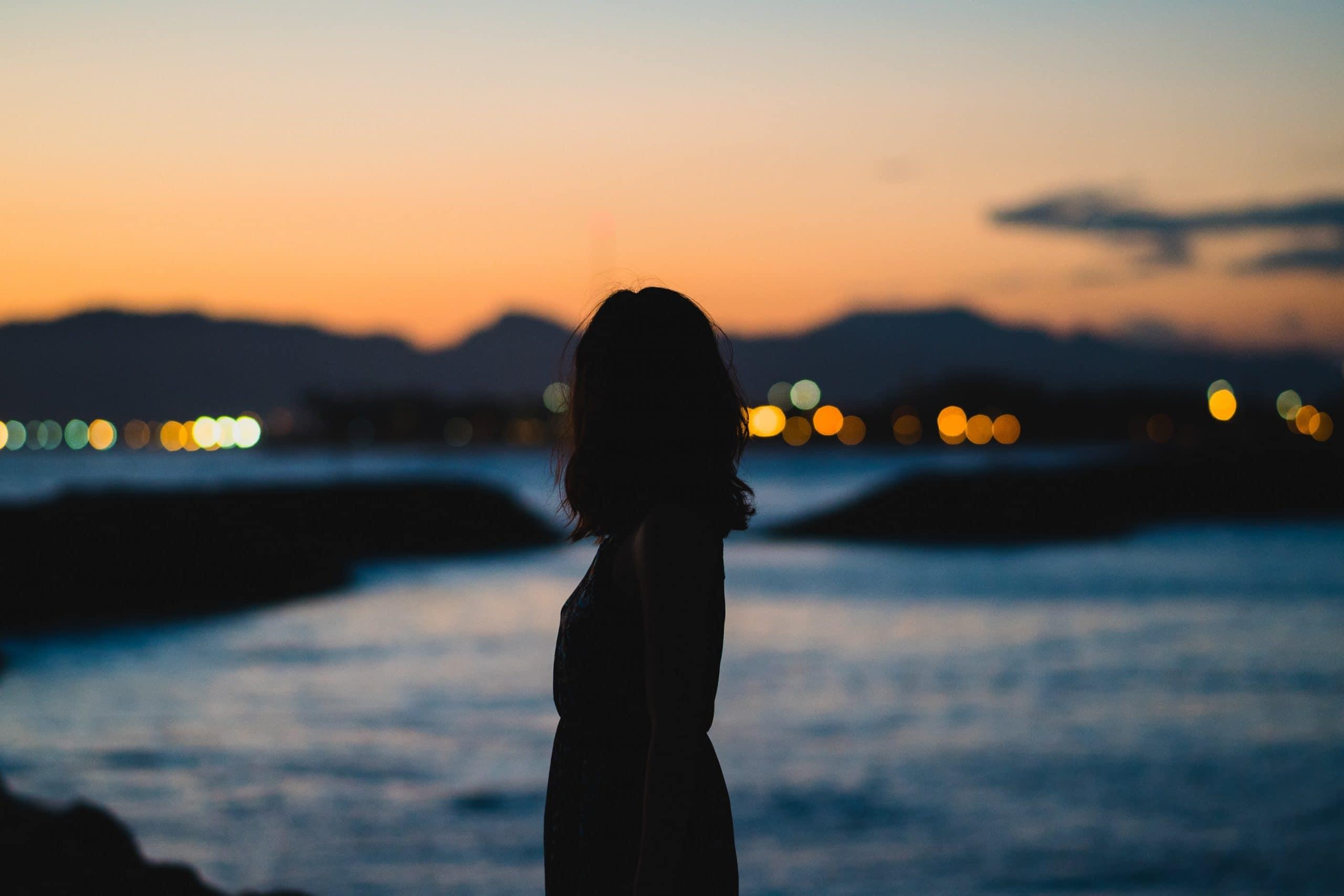 Mulher olhando para cidade no horizonte.
