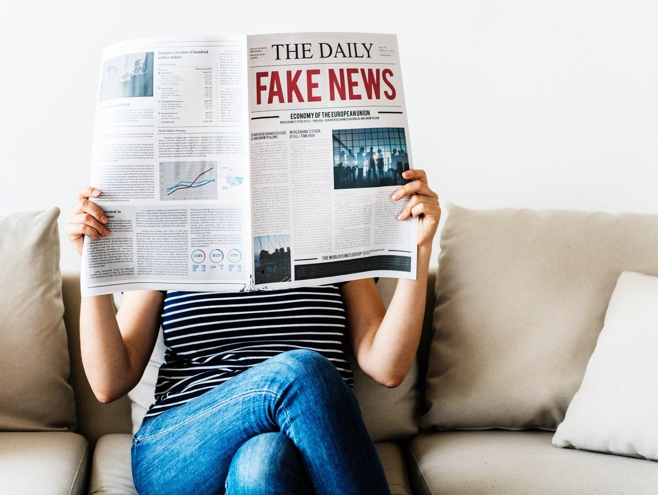 Mulher sentada segurando jornal