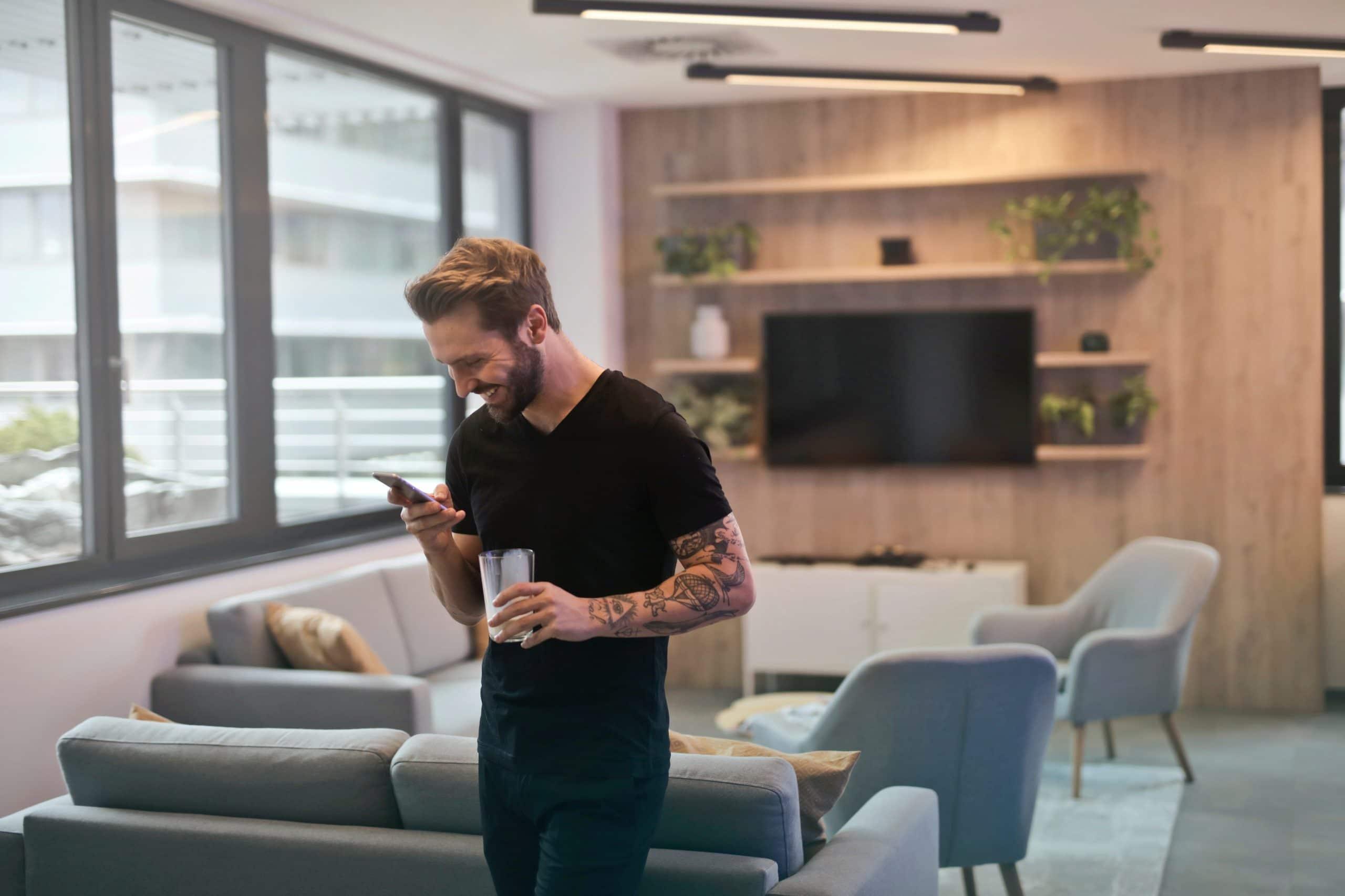 Homem em pé em sala mexendo no celular