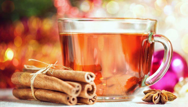Xícara de chá de canela com canelas em volta