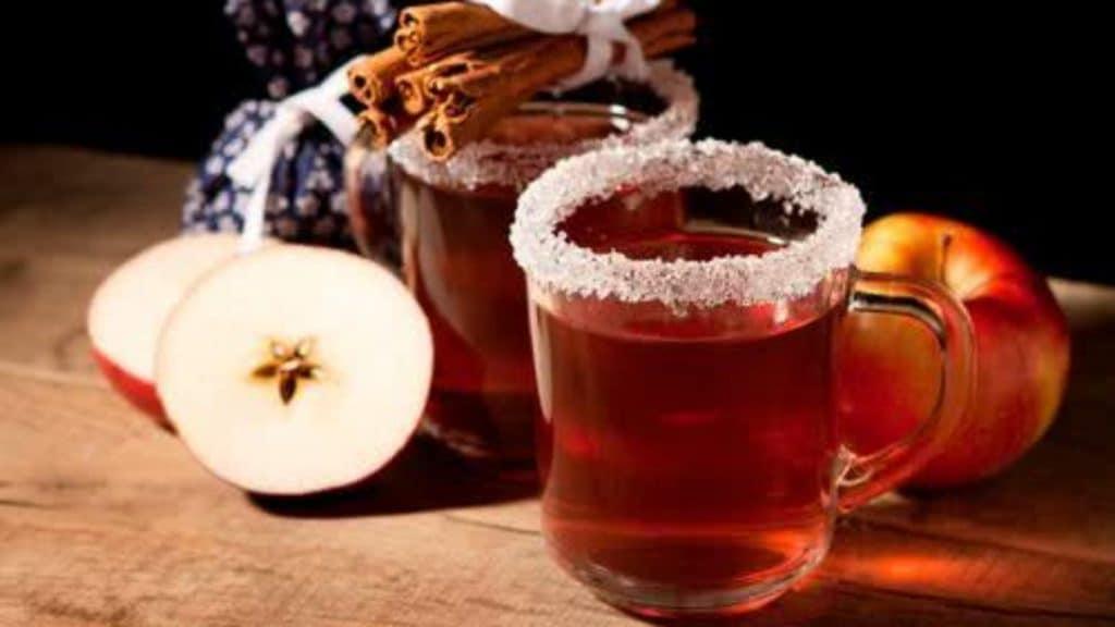 Xícaras de chá com canela e maçãs em volta
