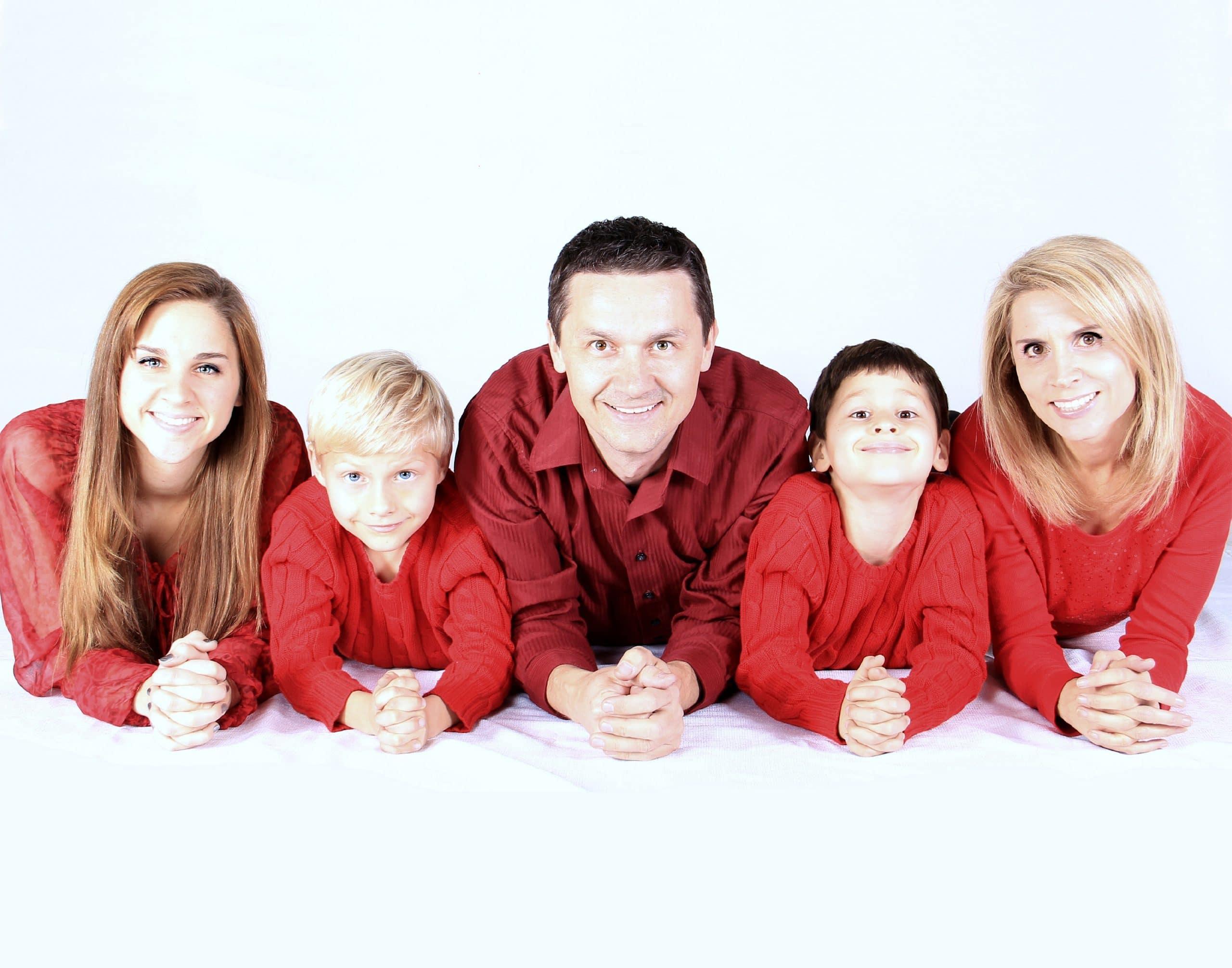 Familia deitada de barriga pra baixo e camisas vermelha