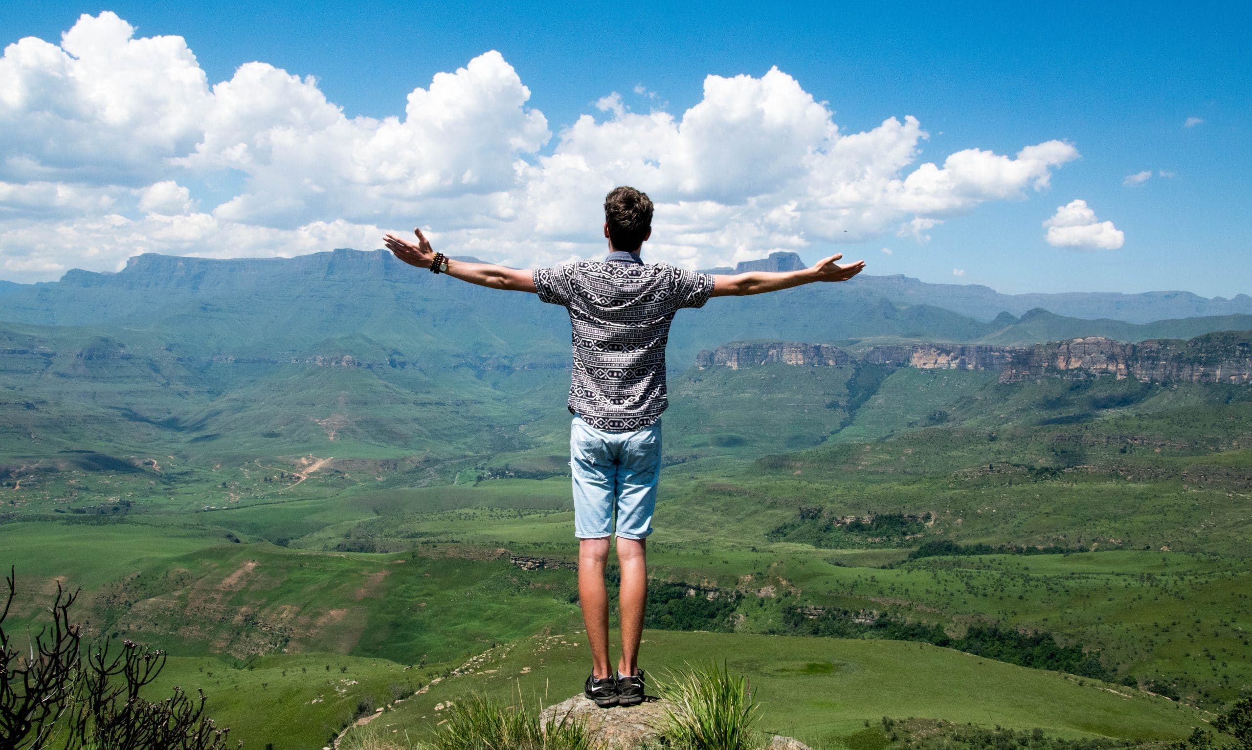 Homem de braços abertos com paisagem ao fundo
