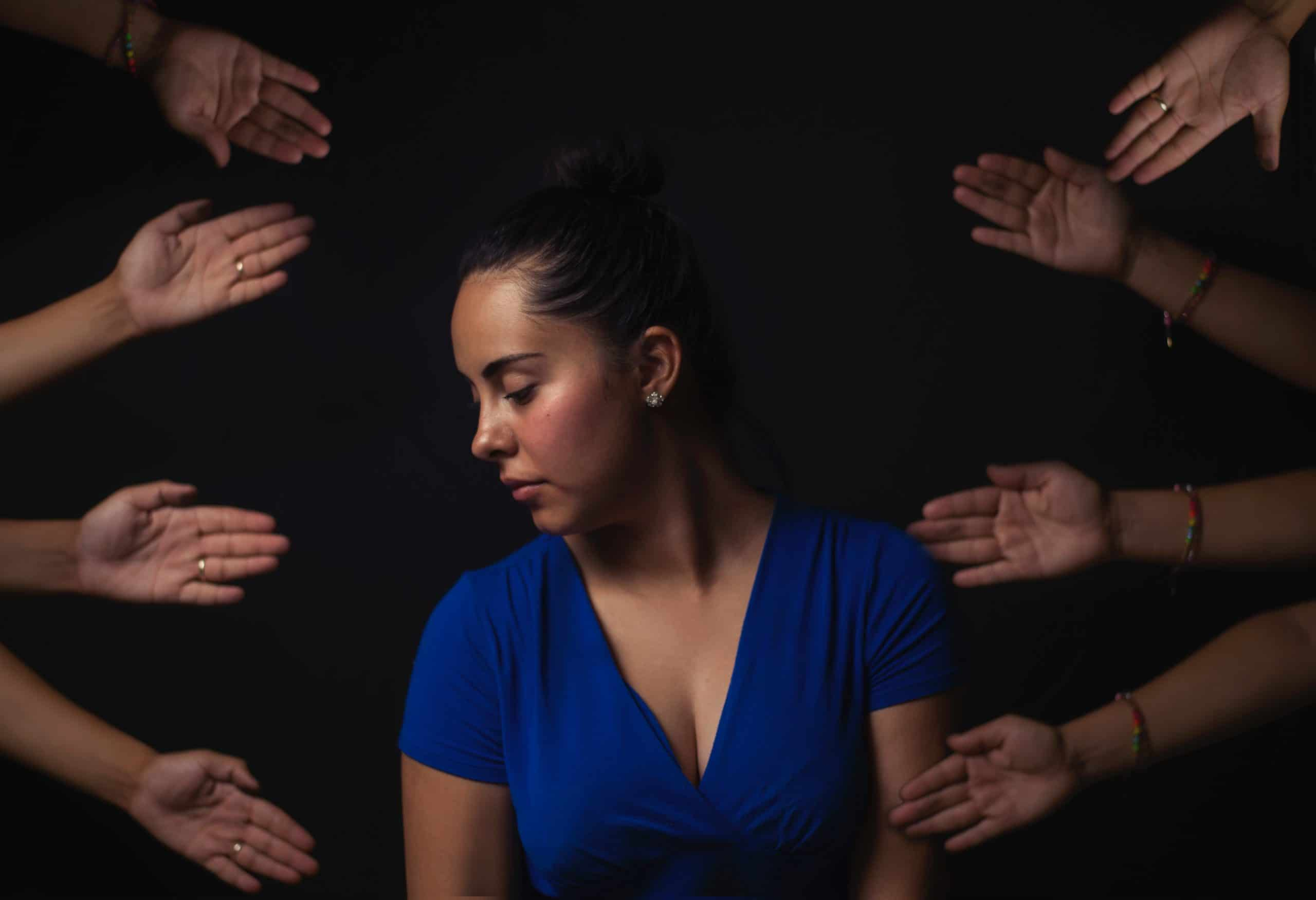 Mulher tensa com mãos à sua volta