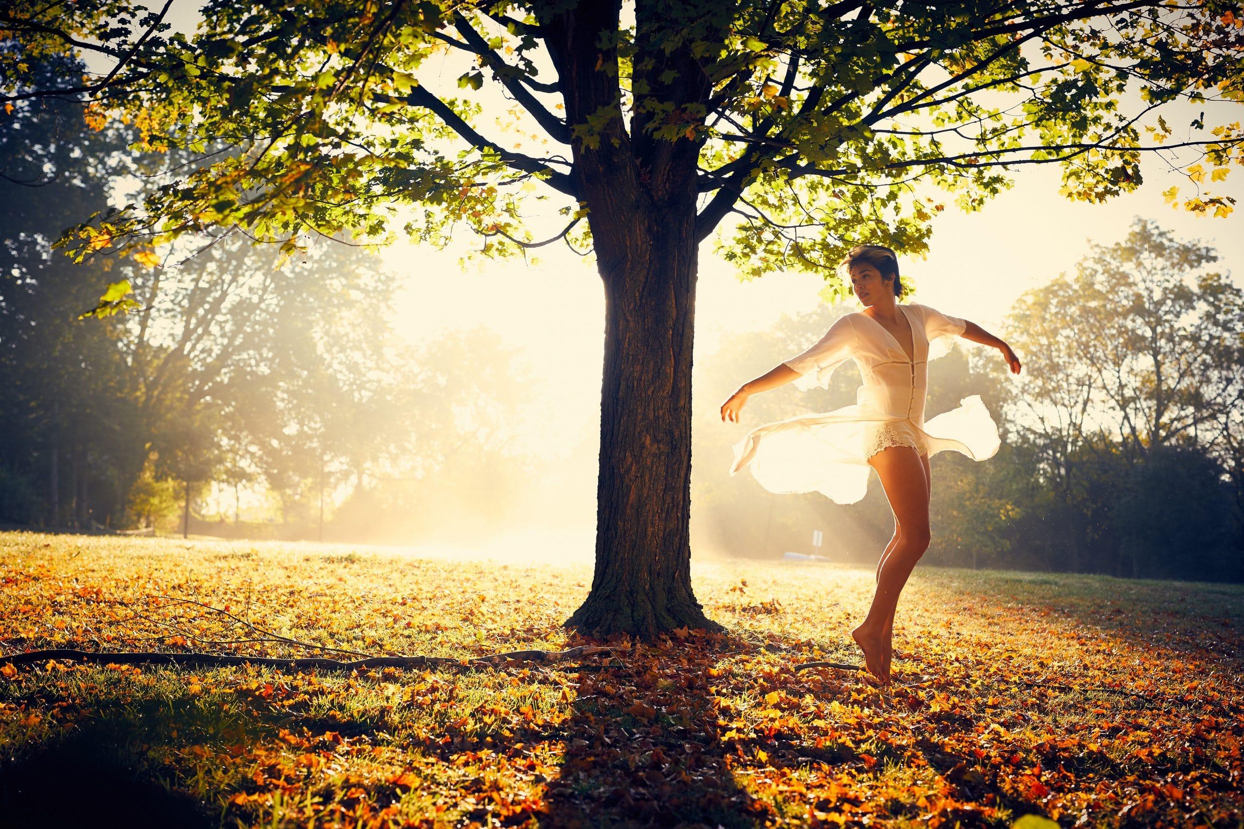 Mulher dançando ao lado de árvore com sol reluzindo