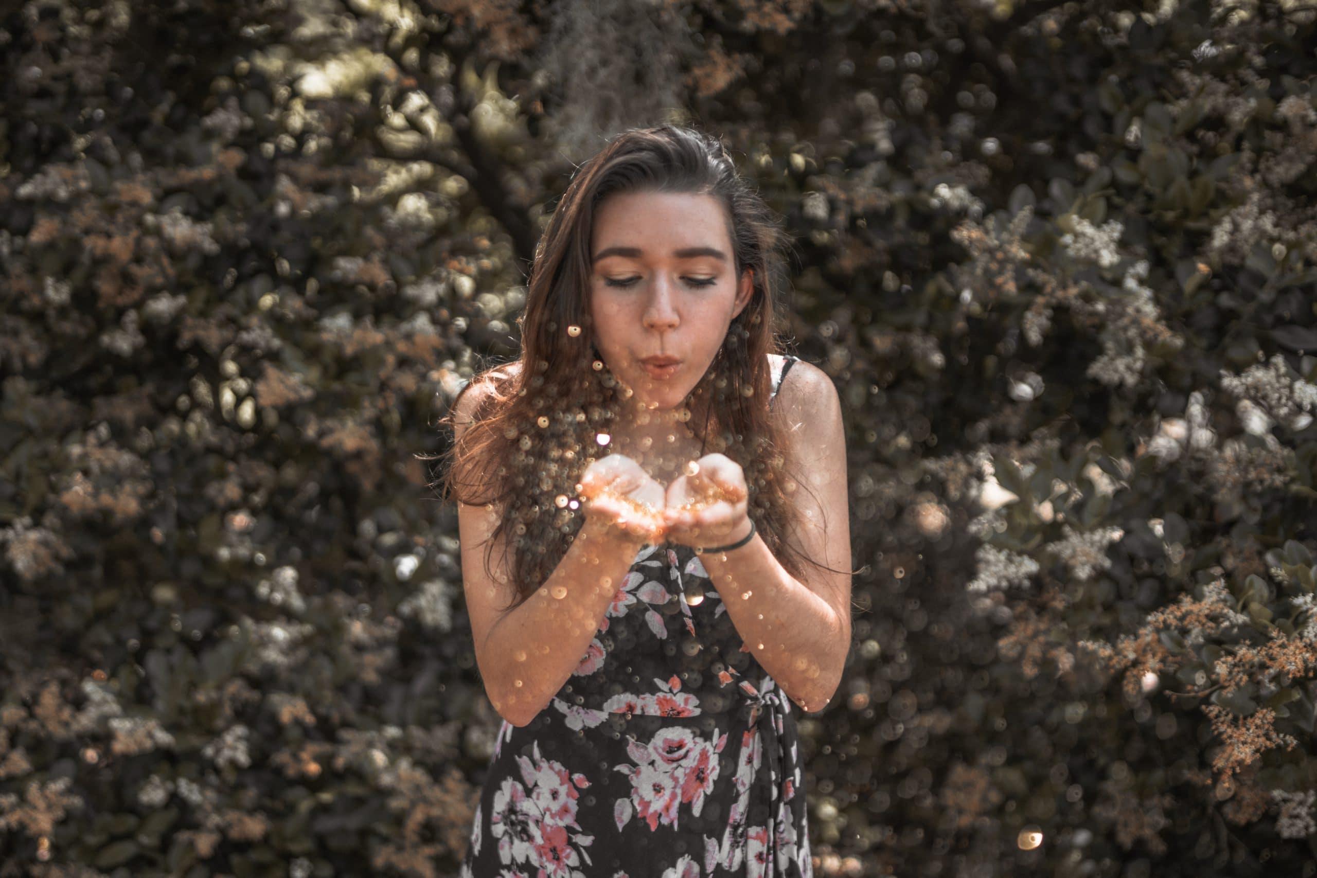 Menina assoprando pós de glitter que estão em suas mãos.