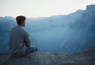 Homem sentado em montanha olhando para o horizonte