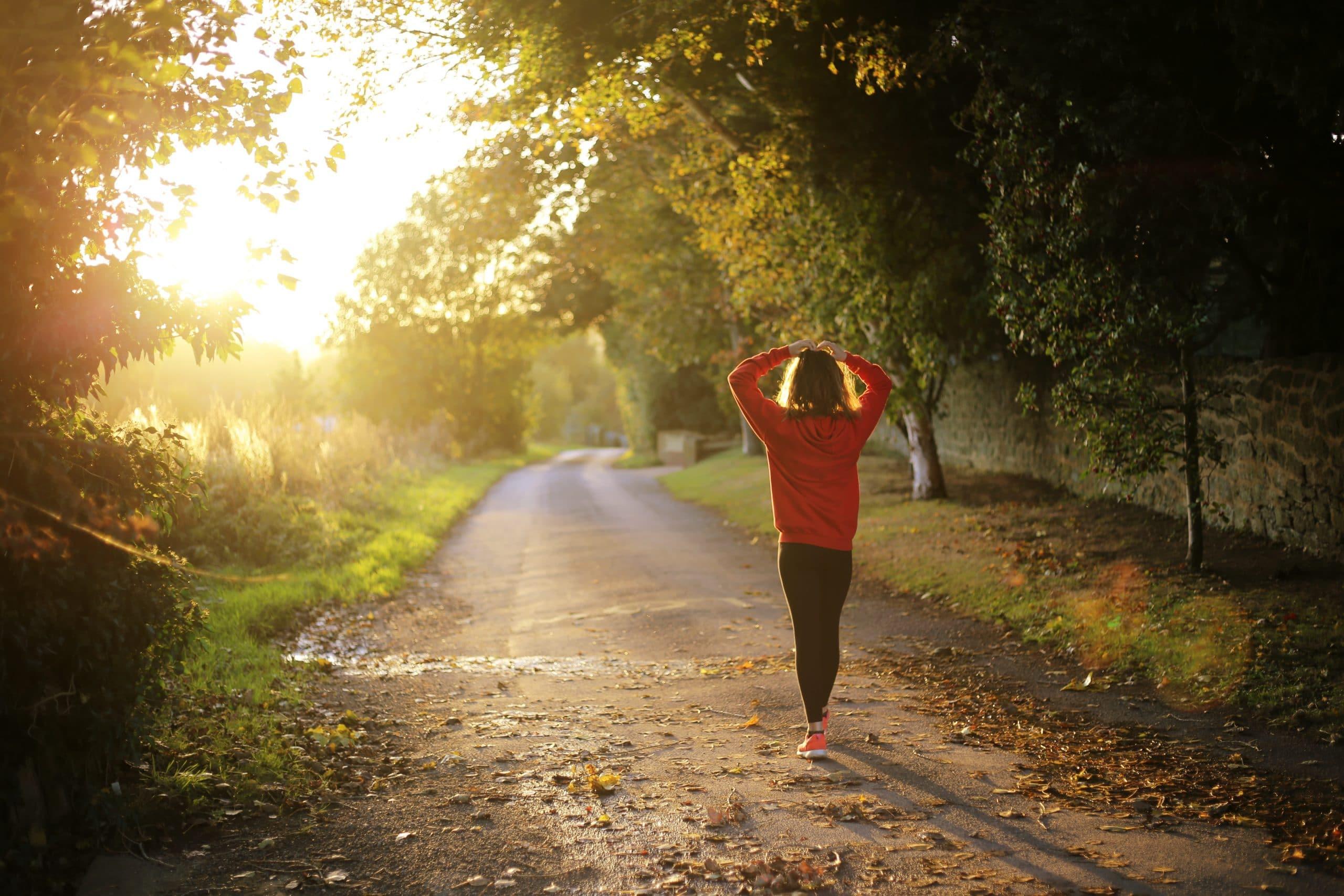 Mulher caminhando diante da luz do sol.