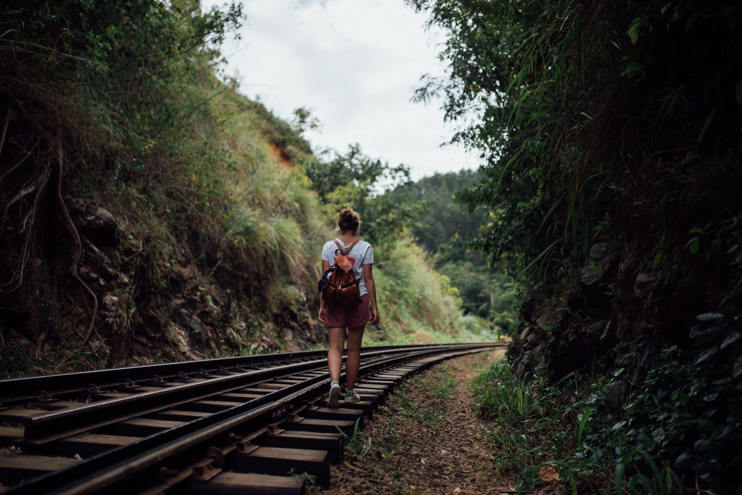 Mulher andando sobre os trilhos do trem.