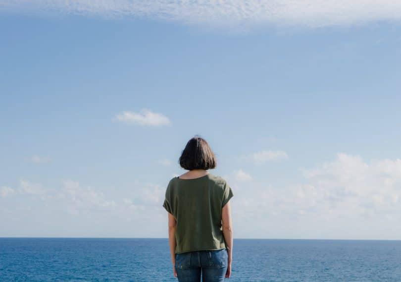 Mulher de costas olhando para o mar