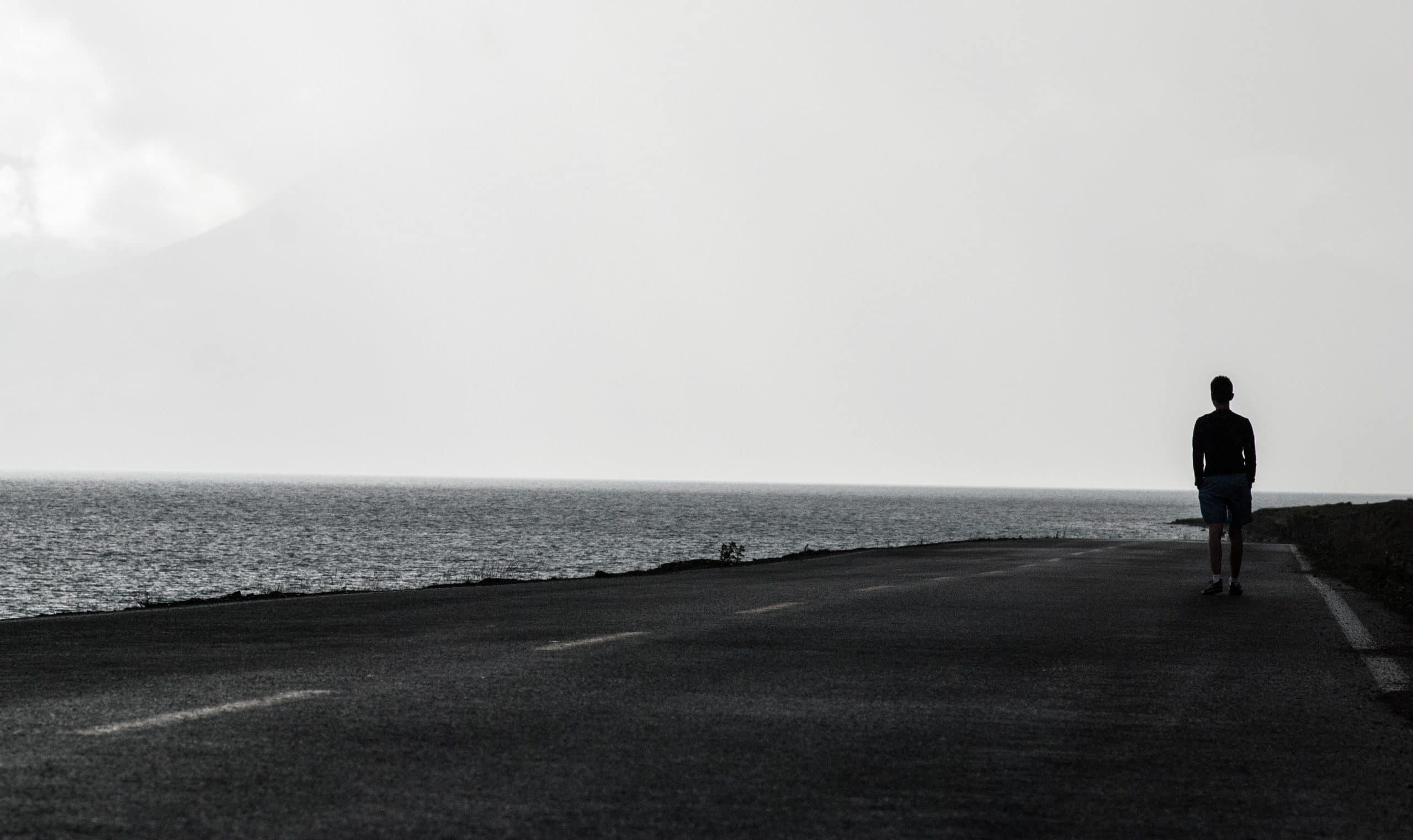 Homem andando em rodovia à beira do oceano.