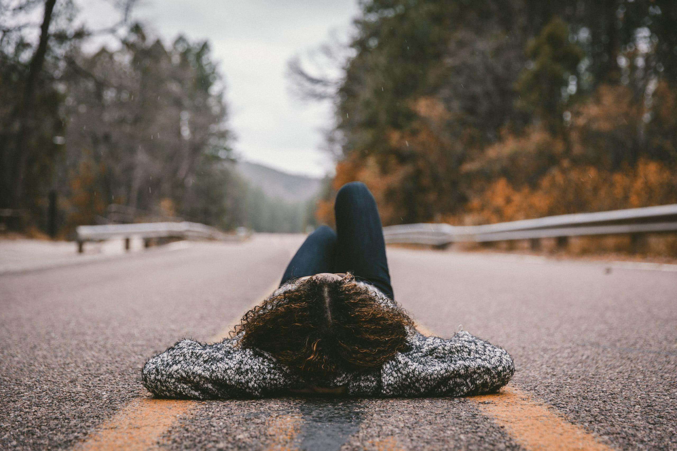 Mulher deitada no meio da estrada