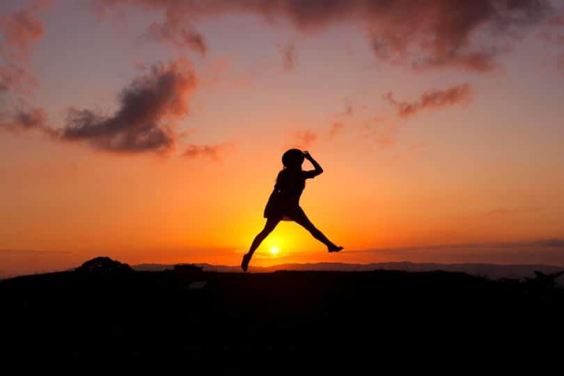 Silhueta de uma mulher saltando.