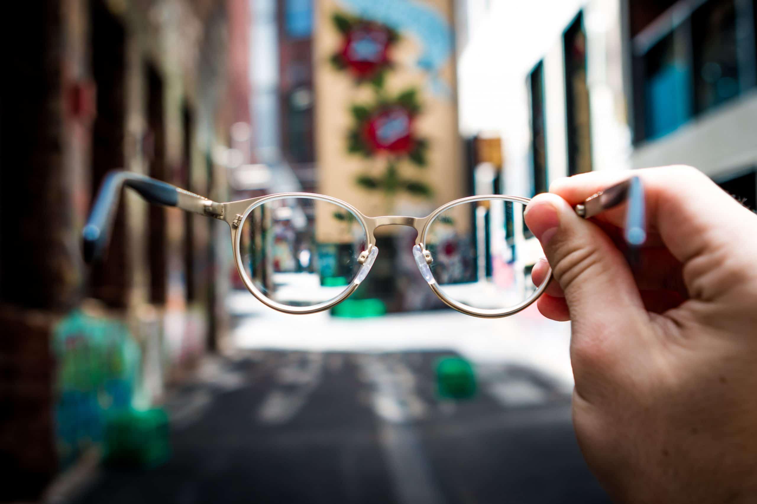 Mão segurando óculos de grau