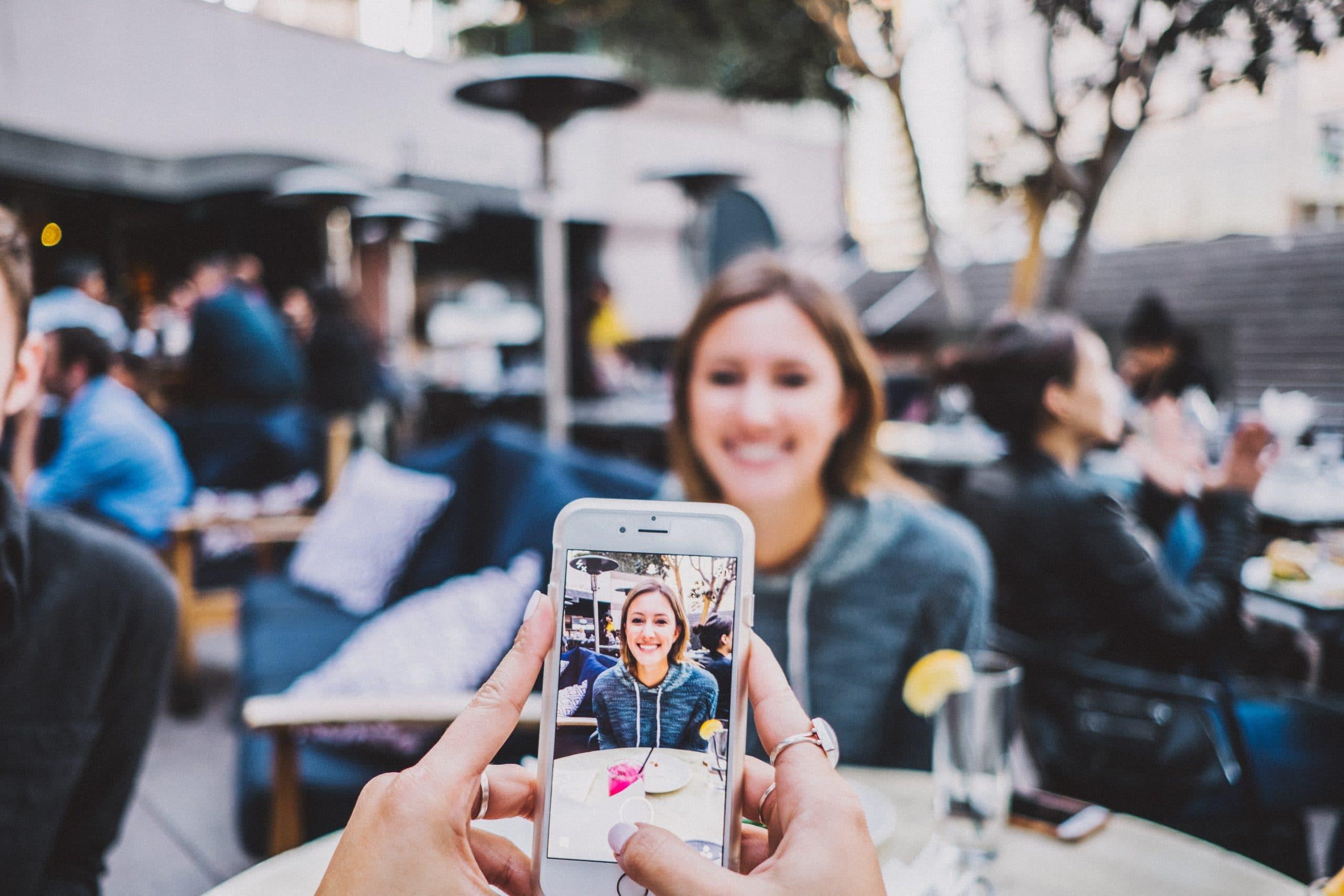Mãos segurando celular tirando foto de mulher