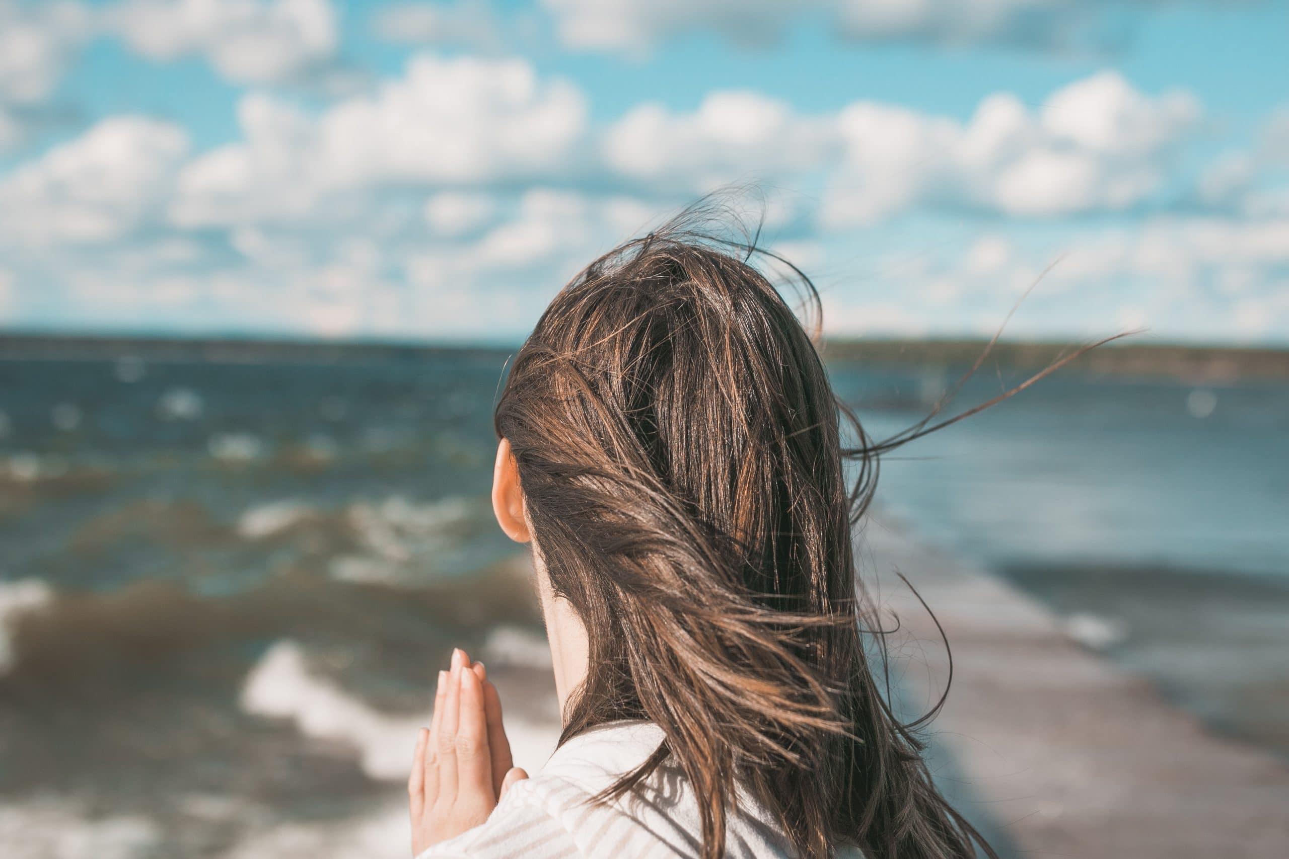Mulher de costas olhando para o mar com as mãos juntas.