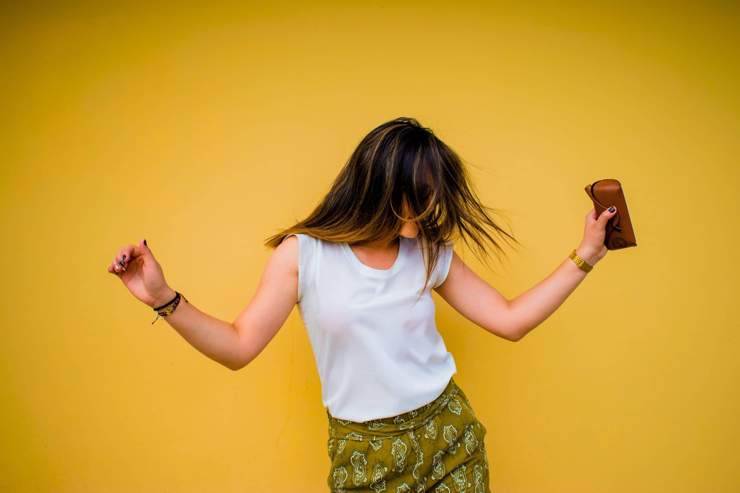 Mulher dançando em fundo amarelo