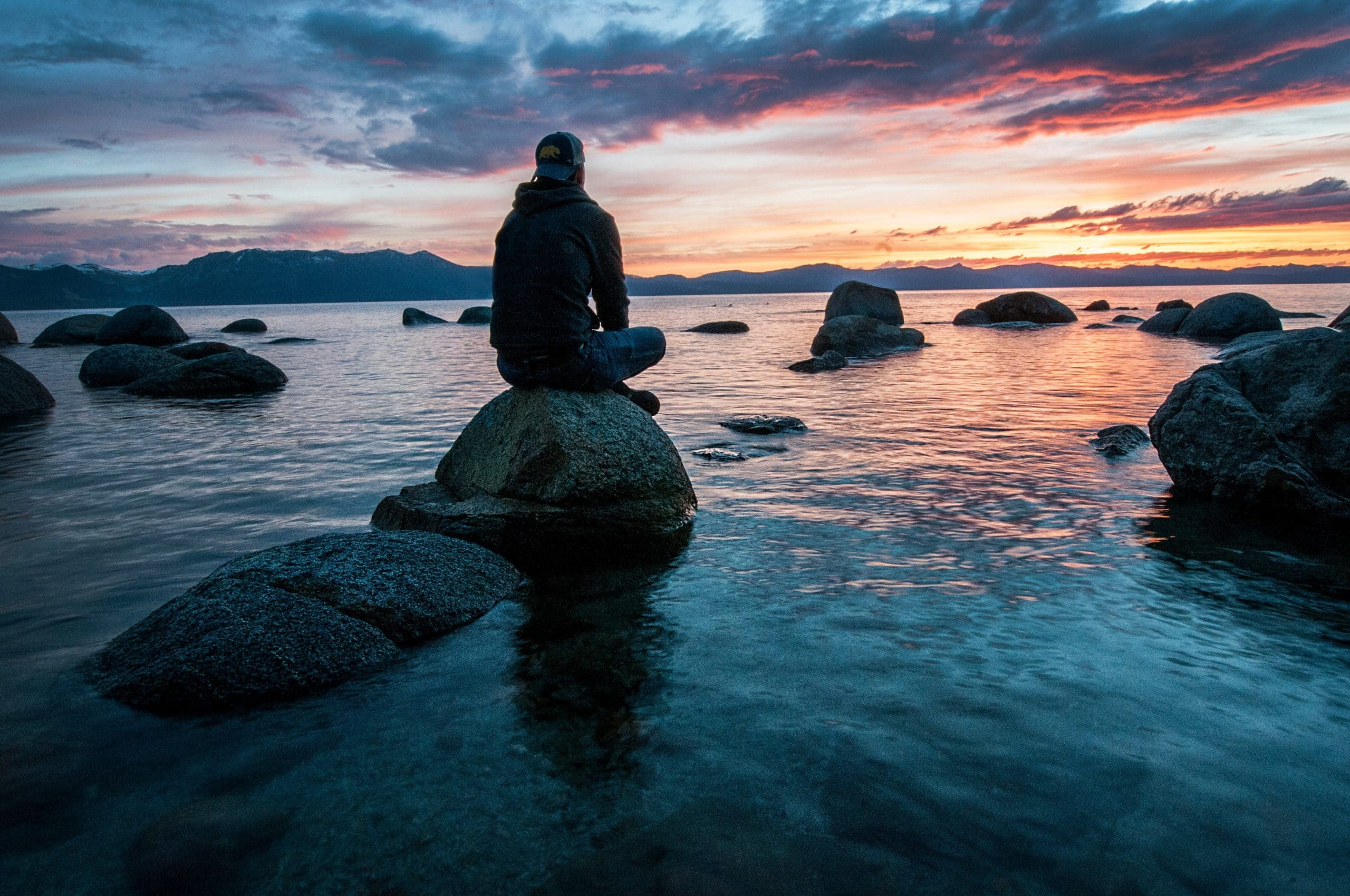 Homem de costas sentado em pedras
