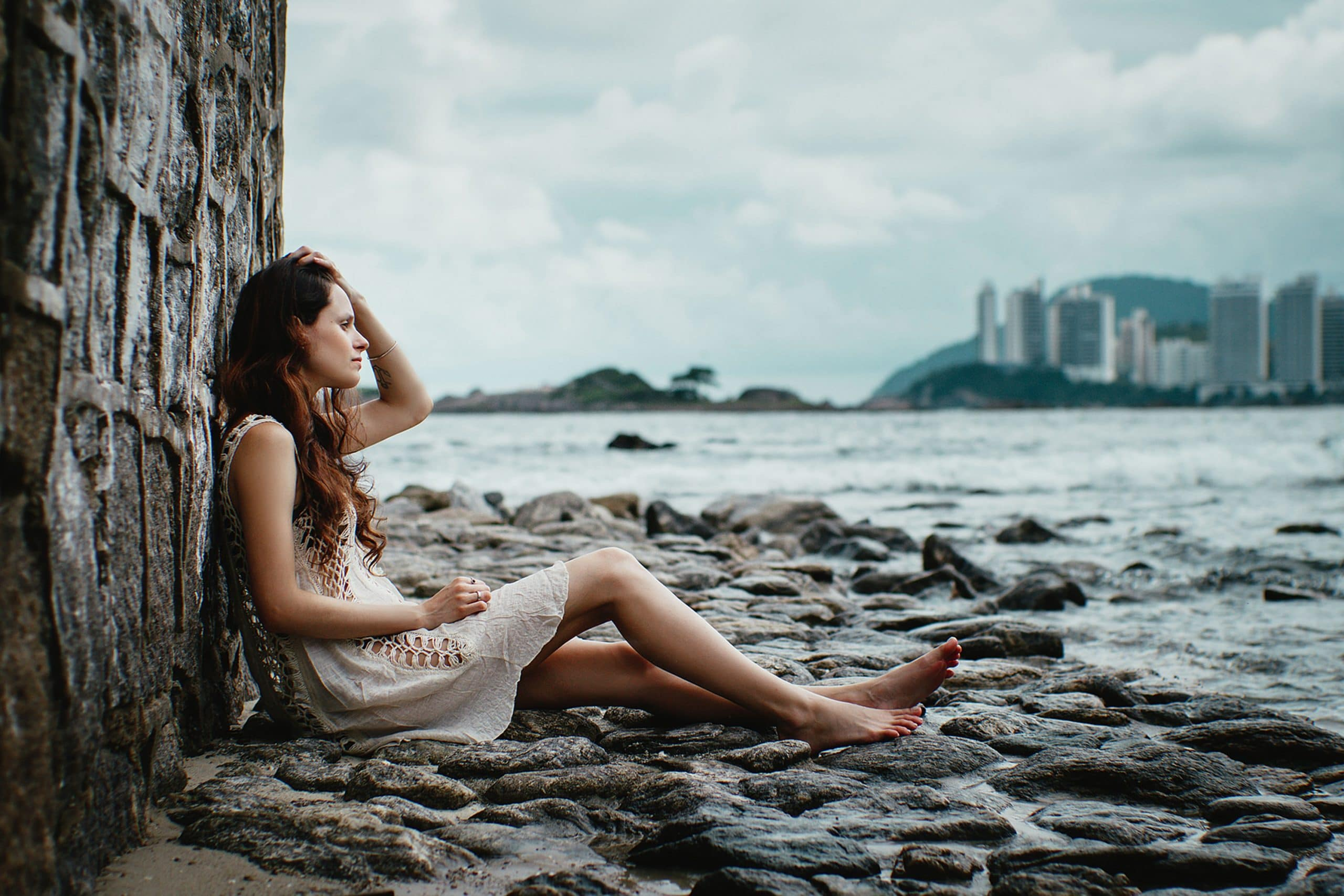 Mulher sentada em pedras com mar ao fundo