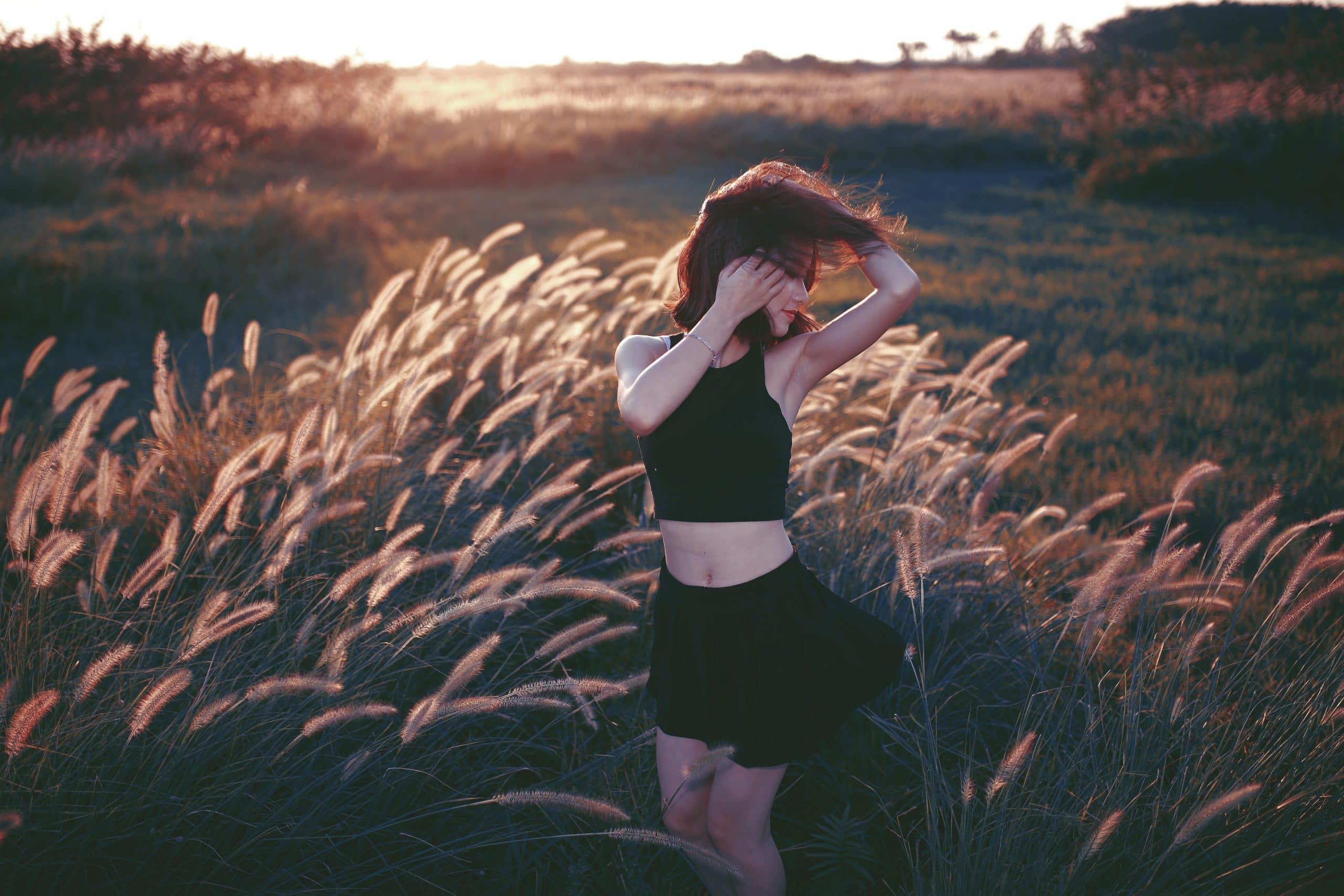 Moça em um campo com seus cabelos voando e corpo em movimento.