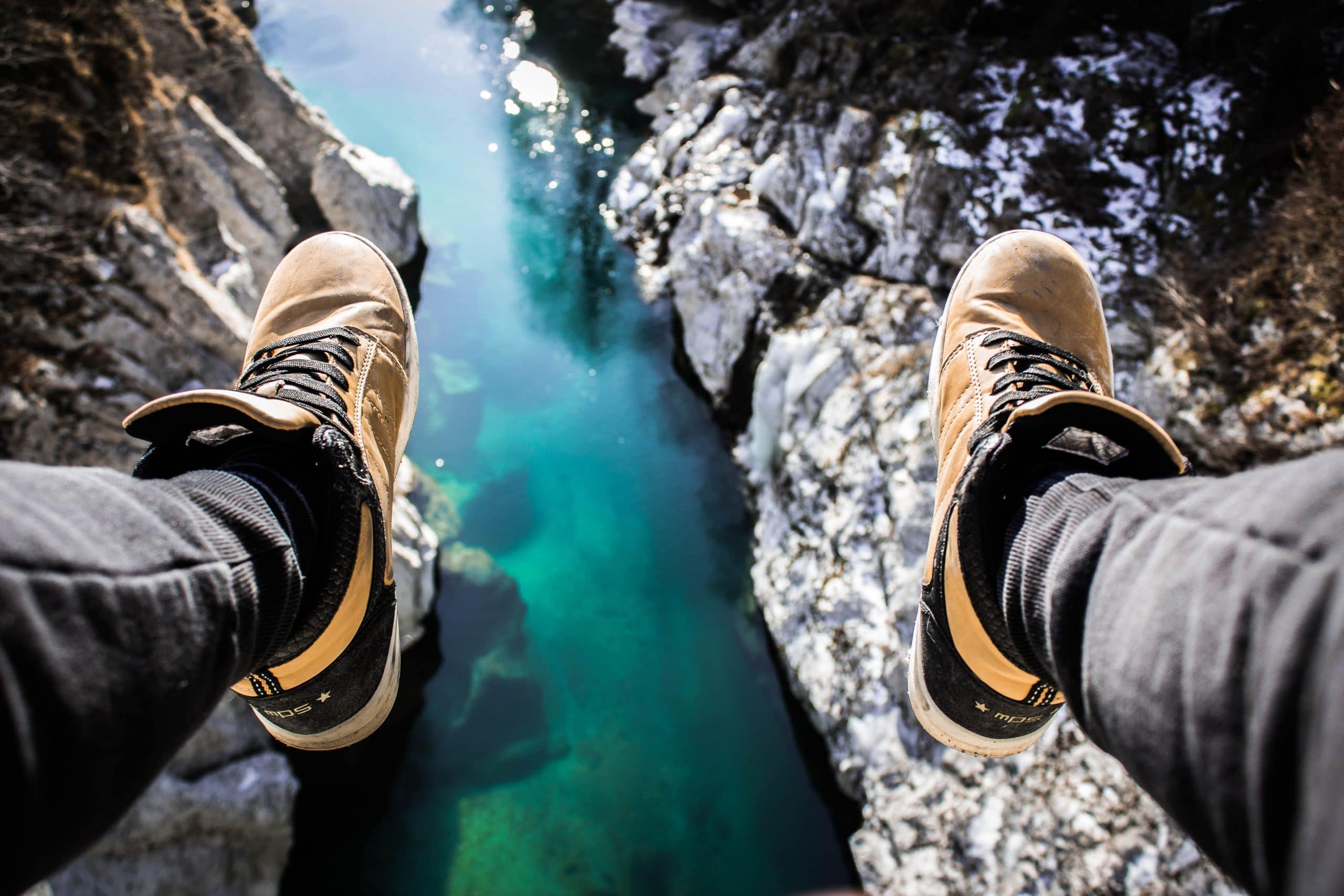 Pés visto de cima com rio e pedras ao fundo