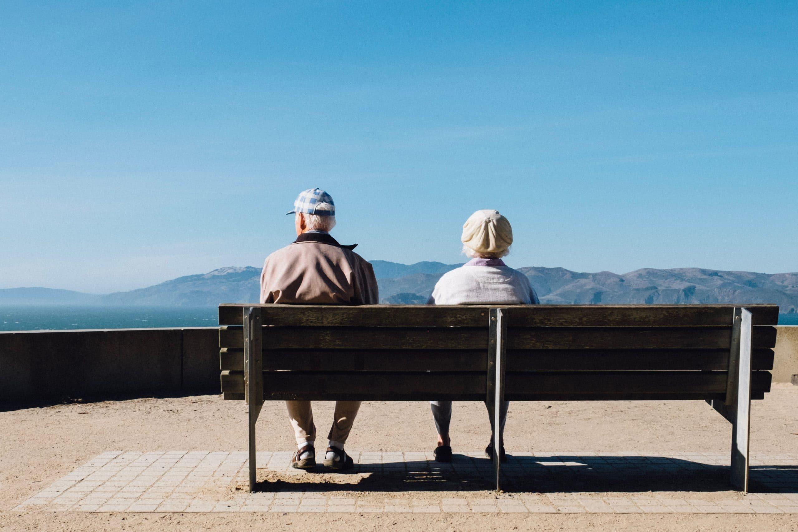 Casal de senhores sentados de costas em banco