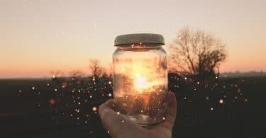 Uma mão segurando um pote de vidro com glitter em frente ao pôr do sol.