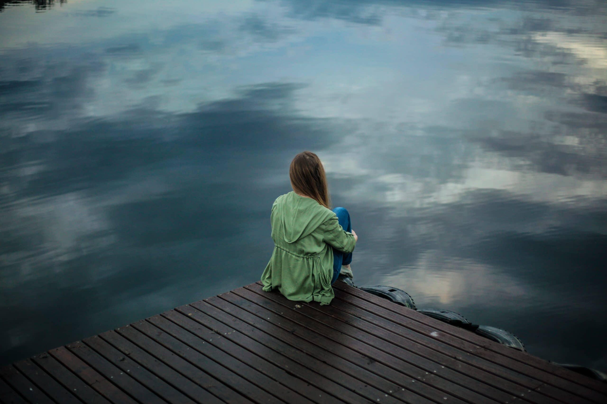 Mulher sentada olhando para lago.