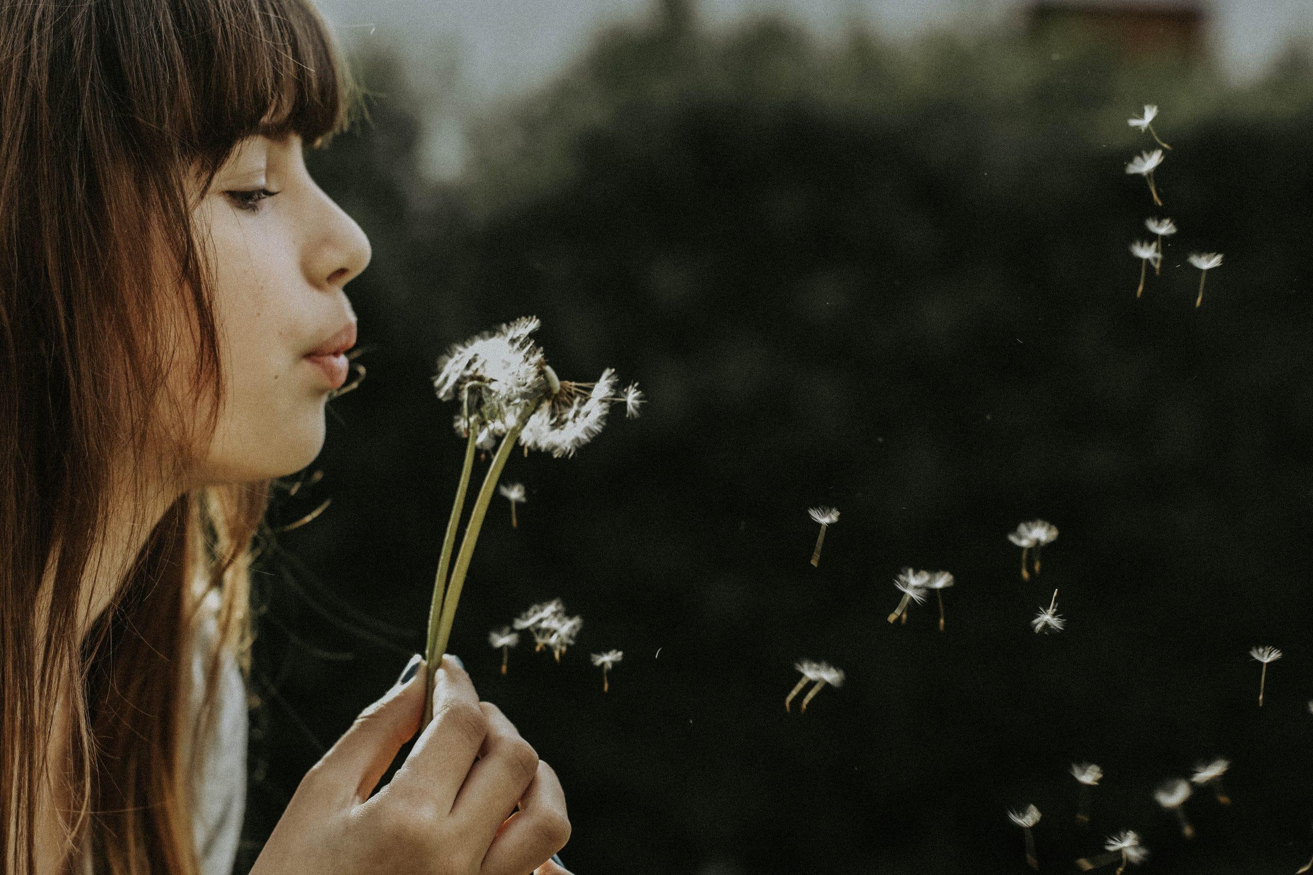 Garota assoprando flor dente-de-leão
