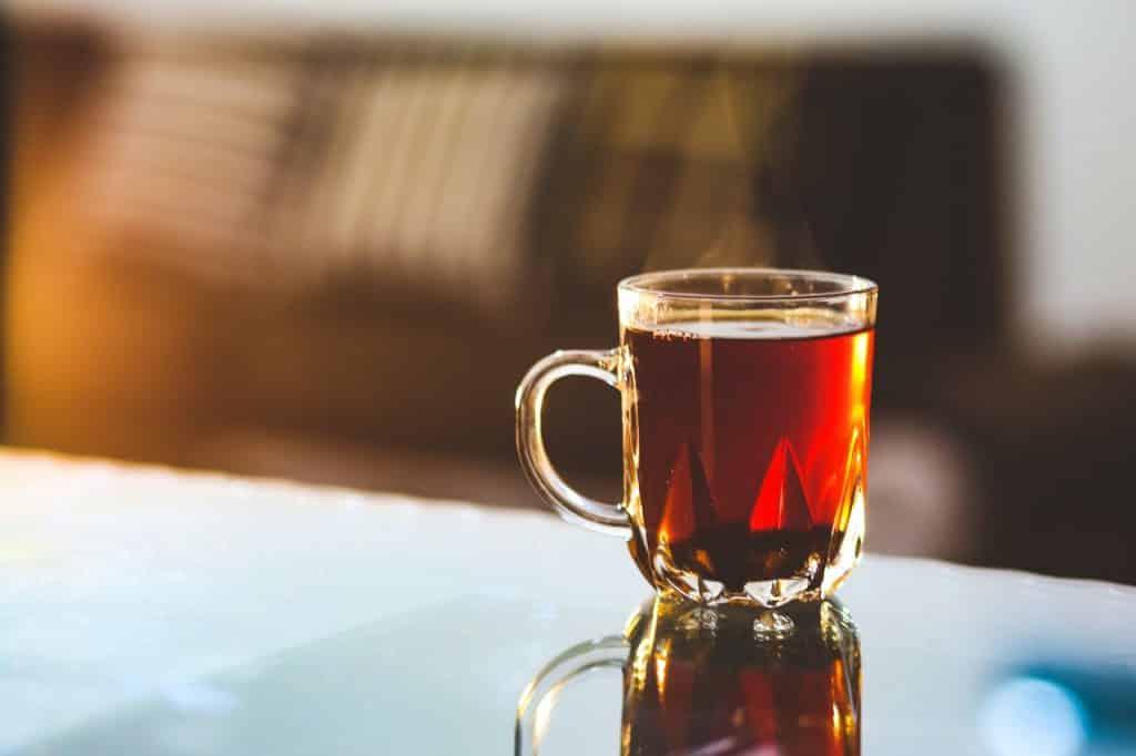 Xícara de vidro com chá quente dentro, sobre uma mesa.