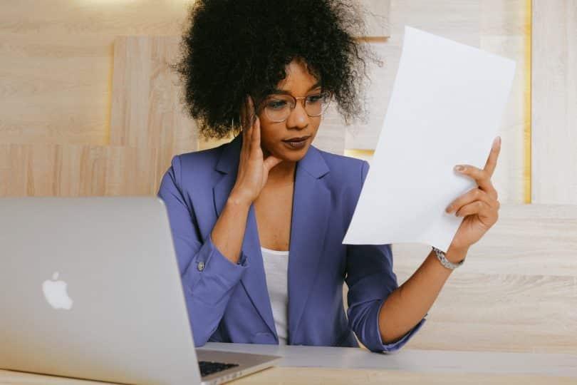 Mulher segurando um relatório na mão. Ela está com o rosto sério.