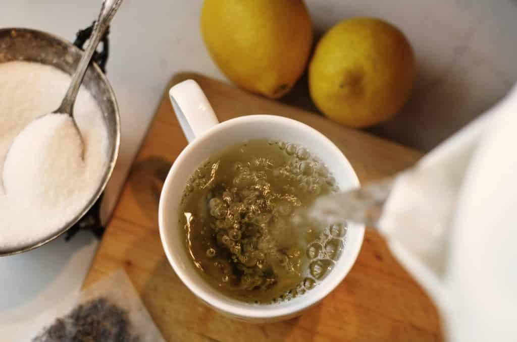 Água quente sendo despejada em um xícara de chá