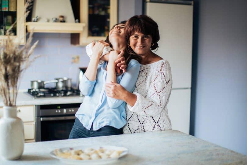 Mulher abraçando sua filha na cozinha