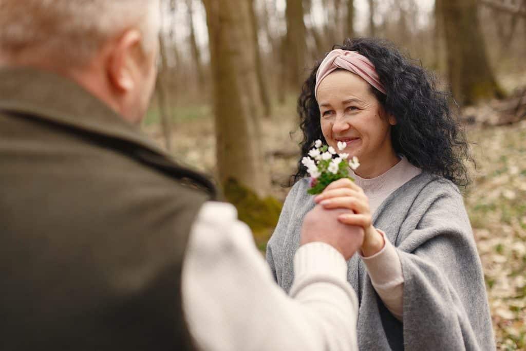 Homem dando flor a mulher a sua frente