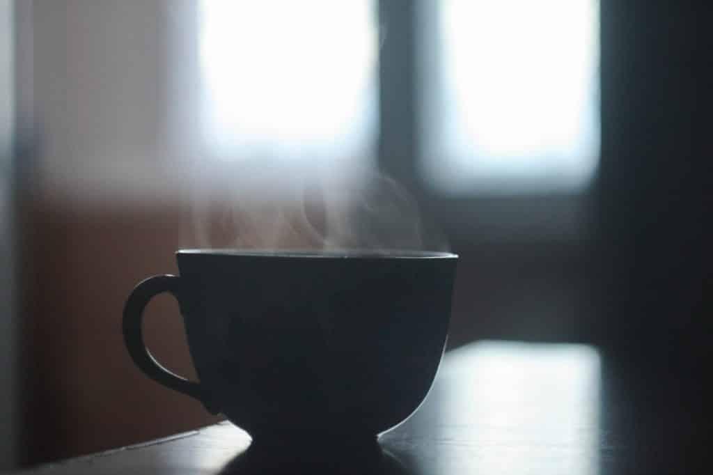 Xícara de chá quente sobre uma mesa.