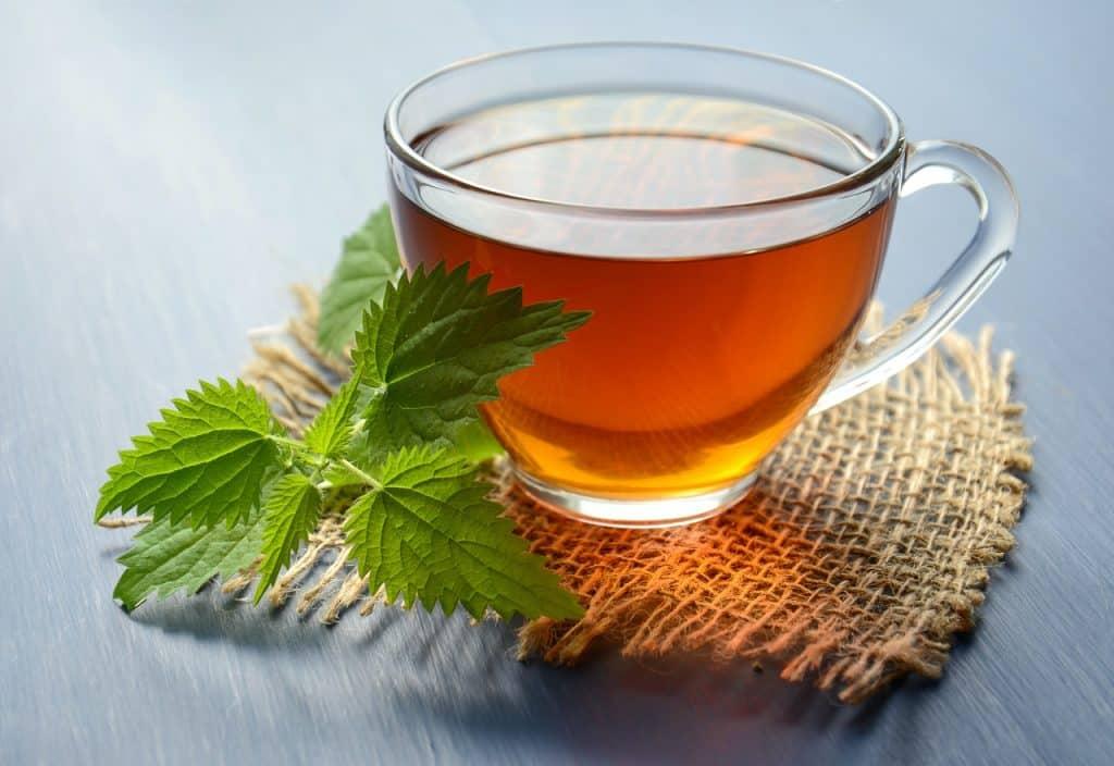 Xícara de chá quente sobre uma mesa ao lado de folhas de hortelã