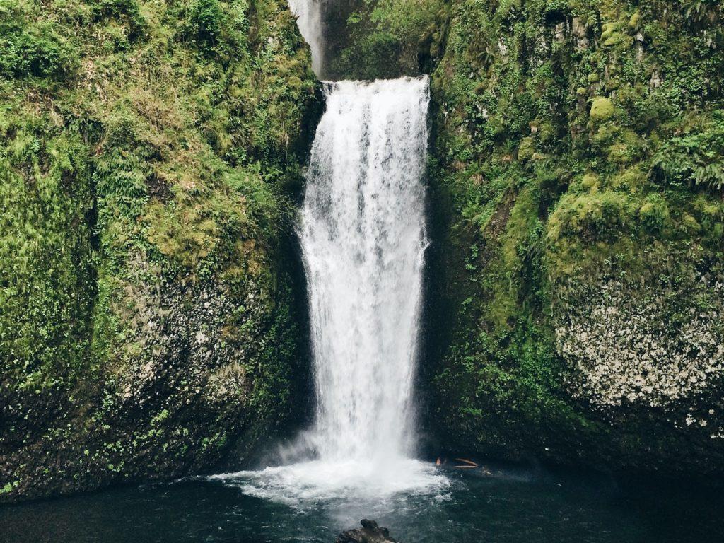 Imagem de uma cachoeira entre rochas vista durante o dia.