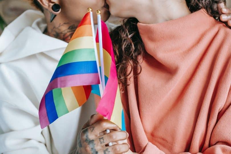 Casal de mulheres se beijando e segurando bandeira LGBT+